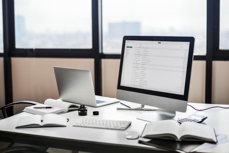 Escritorio con ordenador y cuadernos. Cómo mejorar el SEO de tu tienda online.